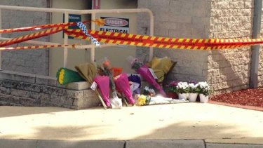 Flowers have been placed at the site of the blast that killed two people and left two others in a critical condition