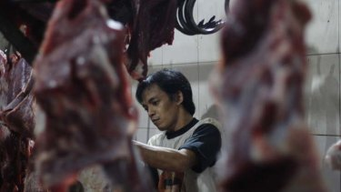 A worker butchers beef in the Gondrong abattoir where Australian cattle were filmed being mistreated.