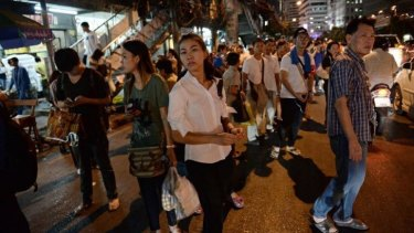 Thai residents wait for transportation to return home home after a curfew was imposed following Thailand's army chief's announcement that the armed forces were seizing power, in Bangkok.