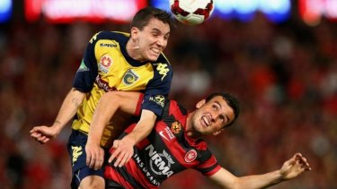 Storm Roux of the Mariners heads the ball over Mark Bridge of the Wanderers during the A-League semi final.