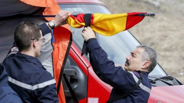 French firefighters tie a black ribbon to  a Spanish flag outside a tent where relatives and officials are due to pay tribute to the victims of the Airbus A320 crash.