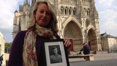 """Naomi Stokes, holding a picture of her great-grandfather Sergeant Charles """"Charl"""" Stokes."""
