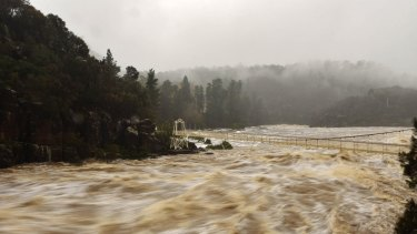 Floodwaters rush under the Alexandria Suspension Bridge in Launceston's Cataract Gorge.