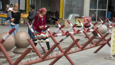 Tightened grip: Uighur women walk past barricades at the entrance to a shopping district in the city of Aksu, Xinjiang province.