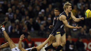 Under pressure: Carlton's Dennis Armfield gets a handball away at Etihad Stadium despite Mathew Stokes's efforts, but the Cats have maintained their grip on victory over the Blues at the venue for nearly nine years.