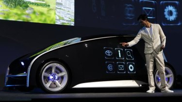 A model presents Toyota's concept vehicle Fun-Vii at a pre-Tokyo Motor show reception in a showroom in Tokyo November 28, 2011.