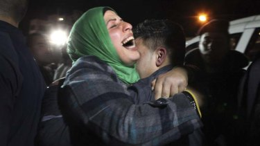 Released … a Palestinian hugs her freed son.