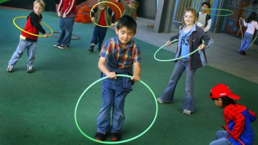 Children enjoy playing with hula hoops in the playground of the Melbourne Museum.
