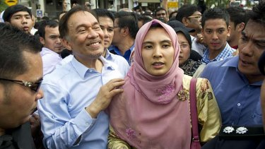 Not guilty ... Malaysian opposition leader Anwar Ibrahim (centre left) celeberates the court decision with his daugther Nurul Izzah (centre right) outside the court in Kuala Lumpur.