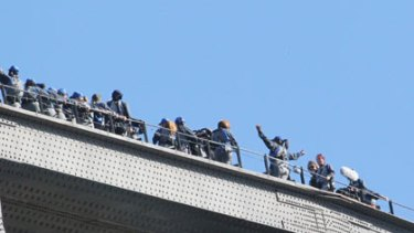 Oprah Winfrey raises her arms for a photo at the top of the Sydney Harbour Bridge.
