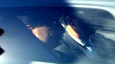 Lloyd Rayney is driven away in a police car after being charged with wilful murder over his wife's 2007 death.