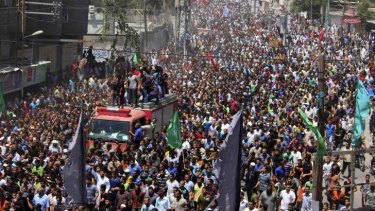 Tens of thousands of Palestinians march in the funeral of three slain Hamas commanders in Rafah in the southern Gaza Strip.