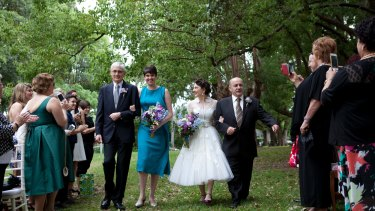 Mick Kyriacou (R) walks his daughter Joy Kyriacou down the aisle, alongside Joy's partner and her father, at her commitment ceremony.