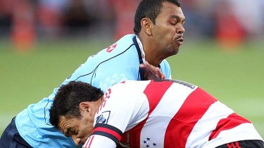 Kurtley Beale of the Waratahs is tackled by Dan Carter of the Crusaders.