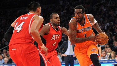 cb76544e6 Knicks forward Amar e Stoudemire drives past Paul Millsap and Gustavo Ayon  of the Atlanta