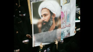 A Saudi protester carries a poster of jailed cleric Nimr Baqir al-Nimr at a demonstration in the eastern Saudi town of al-Awamiya in September 2012.