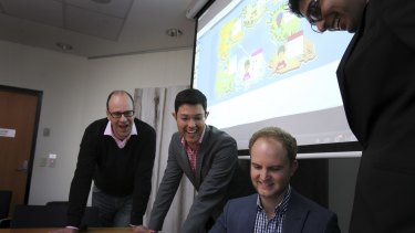 Art of the deal: Dr Robert Jack (far left) and Dr Mauricio Marrone with students playing the Traders of Macquarie University game.