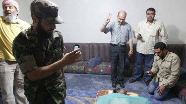 Men take pictures of Muammar Gaddafi's corpse displayed at a house in Misrata