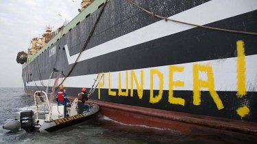 """Greenpeace activists paint """"Plunder"""" on the side of Lithuanian supertrawler Margiris  off the coast of Mauritania."""