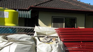 Asbestos stacked in front of a Rocklea house.