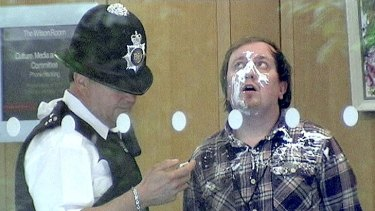 Jonnie Marbles, weairng much of the evidence,  in the hands of police after his pie stunt.