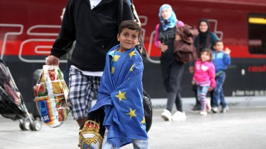 A migrant boy wrapped in an EU flag arrives from Austria at Munich Hauptbahnhof main railway station in Munich, Germany.