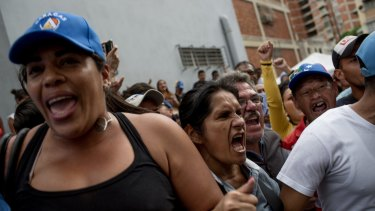 A woman who had been standing in line outside a centre in Caracas that certifies signatures for a referendum to recall President Nicolas Maduro shouts slogans against Venezuela's government after learning that the centre had closed.