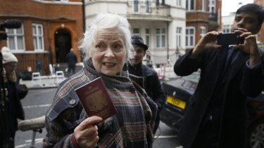 British Fashion designer Vivienne Westwood shows her passport to the media as she arrives outside the Ecuadorean embassy in London on Thursday.