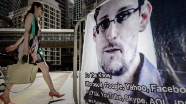 A woman walks past a banner displayed in support of US whistleblower Edward Snowden in Hong Kong.