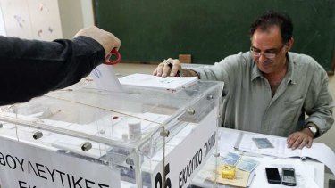 A voter casts his ballot at a polling station in Athens.