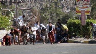 Yemenis run from gunfire at an army base in Aden.
