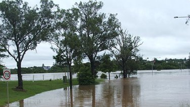 The flooded Mary River on Exhibition Road, Gympie, today, where two bridges have been submerged by water.