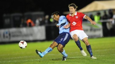 Sydney FC star Nick Carle gets away from Canberra FC's Callum Smith.