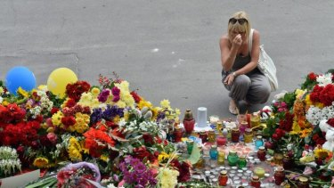 A woman crosses herself after laying flowers outside the embassy.