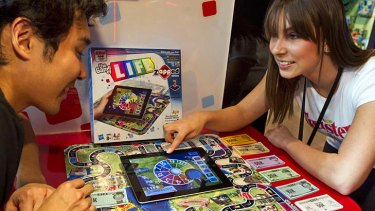 """Demonstrators Trevor Zhou and Aubree Marchione use an iPad to play """"The Game of Life zAPPed"""" at Hasbro's American International Toy Fair showroom in New York last month."""