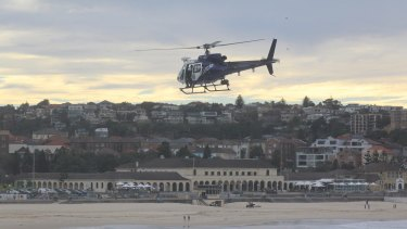 A police helicopter hovers above the water at Bondi Beach.