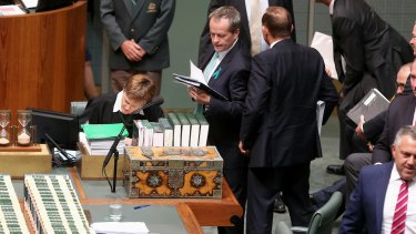 Opposition Leader Bill Shorten tries to squeeze past Prime Minister Tony Abbott to get back to his seat, after a division during question time.