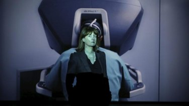 <i>People Like Us</i> curator Felicity Fenner stands in front of Yuri Ancarani's video installation of a robot performing surgery.