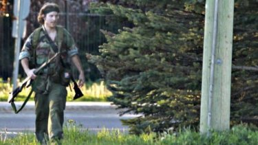A heavily armed man that police have identified as Justin Bourque walks on Hildegard Drive in Moncton, New Brunswick, after several shots were fired in the area.