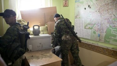 Pro-Russian rebels inspect the offices of an Ukrainian border troops military unit in Luhansk, eastern Ukraine, after taking it from government forces.