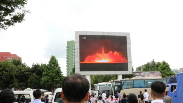 People watch a news broadcast on a missile launch in Pyongyang.