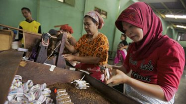 Hand made ... women work in pairs, rolling and cutting kretek cigarettes at a factory in Kudus. Each pair typically makes more than 5000 cigarettes each day.