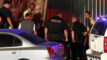 Shot dead ... a victim's body is removed from the Forum Roller World in Grand Prairie, Texas.
