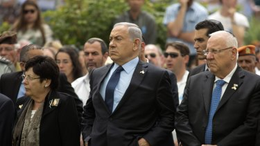 Israeli Prime Minister Benjamin Netanyahu (centre) stands with Israeli President Reuven Rivlin (right) during an official state Memorial Day service for the country's fallen soldiers and victims of terrorism.