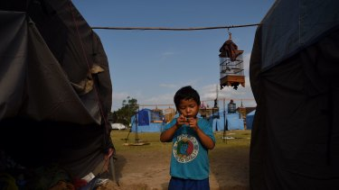 Komang Monda entertains himself amongst the tents at an evacuation camp in Klungkung city, home to thousands of peole who have been evacuated from red zones in preparation for the eruption of Mount Agung, Bali, Indonesia.