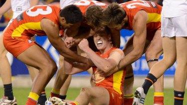 Josh Caddy of the Suns celebrates a goal with team mates.