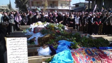 Syrians attend a mass funeral for people whom anti-government protesters said were killed by the shelling in Al Qasseer city, near Homs, last week.