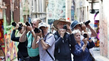 CAPTION: Participants hold their cameras in a laneway off Flinders Street and Flinders Lane on one of the Melbourne Photography Tours, February, 2012.. PICTURE CREDIT: Vincent Long  IMPORTANT USAGE information: This is not a Fairfax Image.   DO NOT ARCHIVE, for use only with story by Katie Cincotta, Thursday, March 1, 2012.