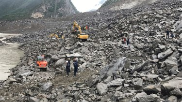 Emergency personnel at the site of a massive landslide in Xinmo village in China.