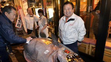 Sushi-Zanmai owner Kiyoshi Kimura poses next to the 269 kilogram bluefin tuna he purchased on the first trading day of the new year at Tokyo's Tsukiji fish market.